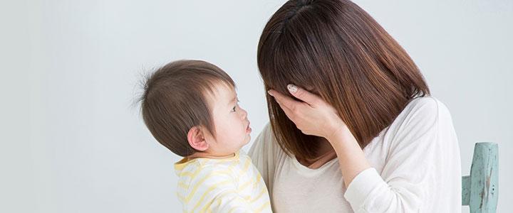 赤ちゃんを抱え病気に悩む母親